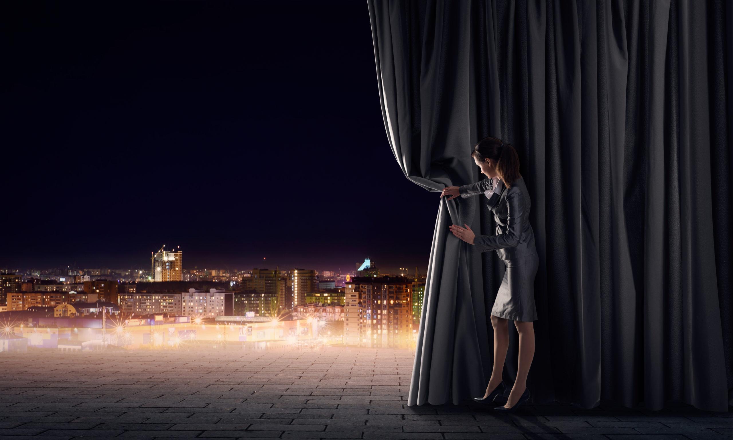 elegante Frau hält Vorhang zu Seite