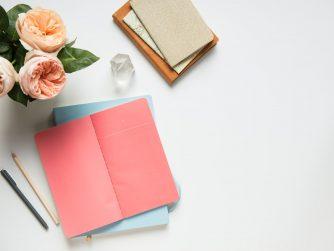 Apricot-Frabenes Tagebuch mit Blumen auf Schreibtisch