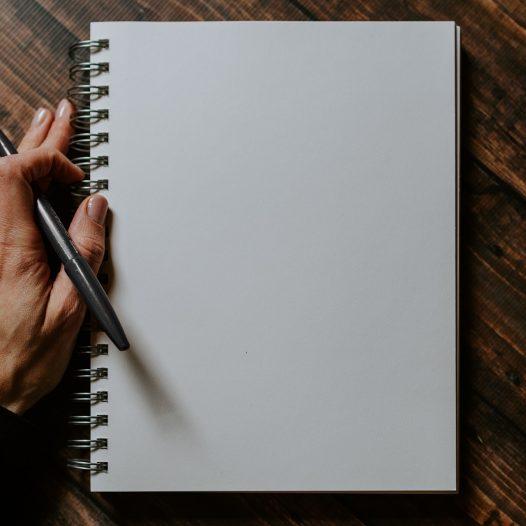 Buch mit Hand, die einen Stift hält