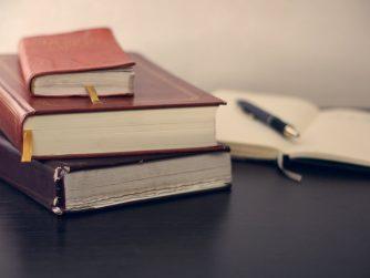 viele Bücher auf Tisch, aufgeschlagenes Buch mit Stift