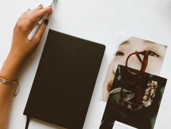 Buch mit Hand und Stift