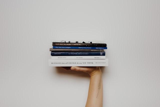 Hand, die mehrere Bücher hochhält